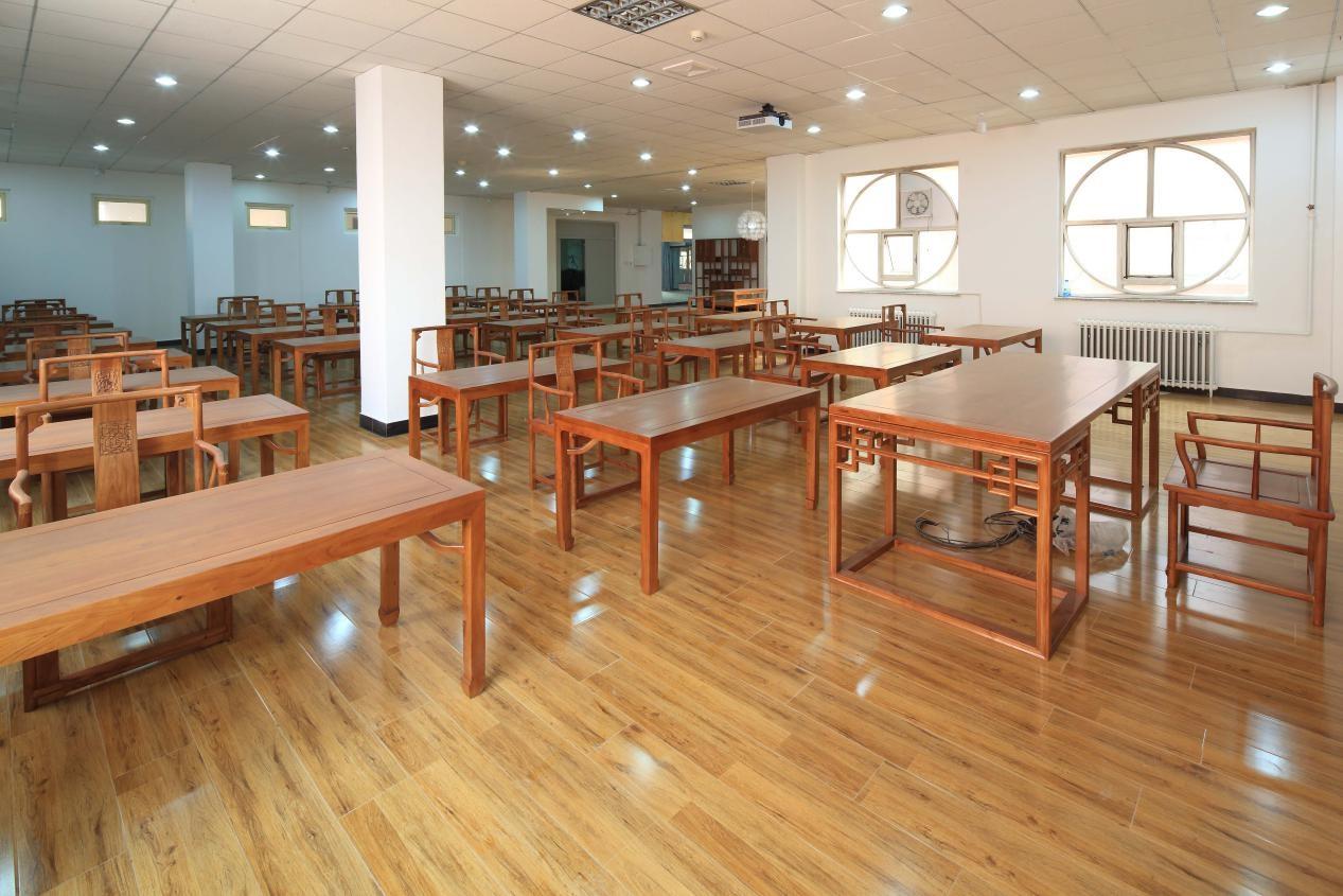 教室内的中式书桌和书法课的主题相映衬,木质仿古书架流露出浓郁的图片